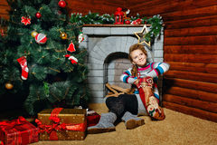 Girl sitting near Christmas tree Stock Photo