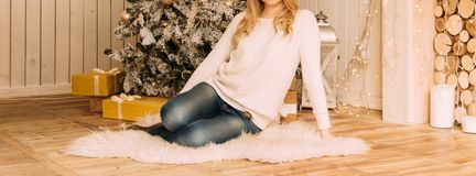 Girl sitting near the Christmas tree, new year, white sweater and jeans stock images