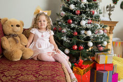 Girl sitting near Christmas tree on sofa with Teddy bear. Royalty Free Stock Photo