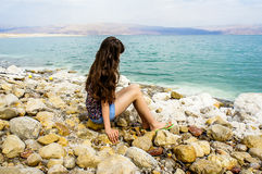 Girl is sitting near the Dead Sea Royalty Free Stock Photo
