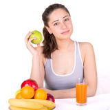 Girl sitting near fruit and holding an apple Stock Photo