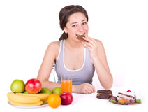 Girl sitting near fruit and sweets and bites chocolate Royalty Free Stock Images