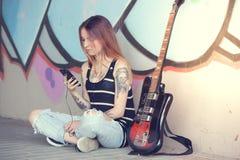 Girl sitting near graffiti wall with a guitar listening music. Stock Photo