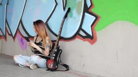 Girl sitting near graffiti wall with a guitar listening music. A girl sitting near graffiti wall with a guitar and listening to music on headphones stock video