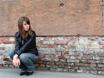 Girl sitting near grunge wall. Sad and Pretty Girl sitting alone near grunge wall stock image