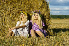 Girl sitting near a haystack Royalty Free Stock Images