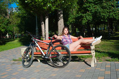 Girl sitting near her bicycle Stock Image