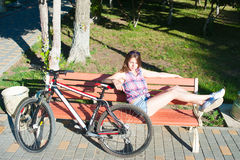 Girl sitting near her bicycle Stock Photography