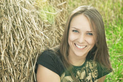 Girl sitting near heystack and smiling Stock Image