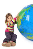 Girl sitting near inflatable globe and holding it Royalty Free Stock Images