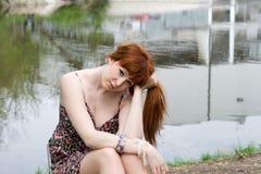 Girl sitting near lake Royalty Free Stock Image