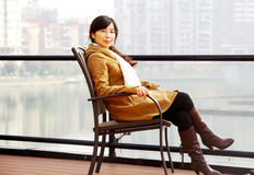 Girl sitting near lake. A grill sits in a chair near lake ,wearing a grey yellow coat Stock Photo
