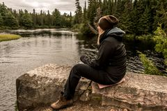 Girl sitting near Lake of two rivers in Algonquin National Park Canada Ontario natural pinetree landscape. Girl with binocular sitting near the Lake of two Royalty Free Stock Photo