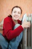 Girl is sitting near oil heater Stock Photo