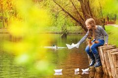 Girl sitting near pond playing with paper boats Stock Image