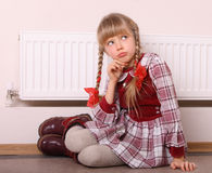 Girl sitting near radiator. Warmth depression. Stock Photos