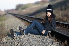 Girl sitting near the rail. A girl sitting near the railway at sunset royalty free stock photo