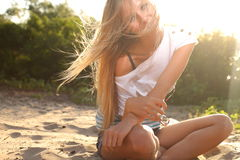 Girl sitting near river against sun Royalty Free Stock Photo