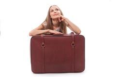 Girl sitting near a suitcase Stock Photos