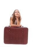 Girl sitting near a suitcase Stock Images