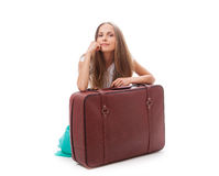 Girl sitting near a suitcase Stock Photography