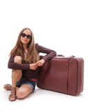 Girl sitting near a suitcase, isolated on white Royalty Free Stock Photography