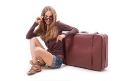 Girl sitting near a suitcase, isolated on white Royalty Free Stock Image