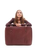 Girl sitting near a suitcase, isolated on white Stock Photos