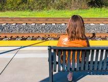 Girl Sitting Near Train Rails Stock Photo
