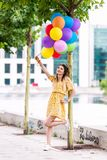 Girl sitting near a tree with a lot of ballons stock images