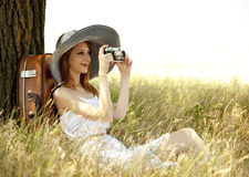 Girl sitting near tree with vintage camera. Stock Photos