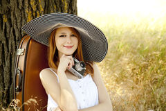 Girl sitting near tree with vintage camera. Royalty Free Stock Image