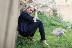 Girl sitting near the wall Stock Photos