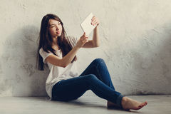 Girl sitting near the wall and looks in Tablet. Beautiful girl sitting near the wall and looks in Tablet Stock Photo
