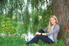 The girl sitting near willow near the lake. Stock Photo