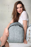 The girl sitting next to a backpack Royalty Free Stock Photos