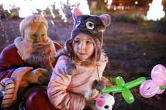 Girl sitting next to the Santa Claus statue Royalty Free Stock Photography
