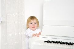 Girl sitting next to a white piano Royalty Free Stock Image