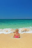 Girl sitting in the ocean breaking waves on the sand beach Royalty Free Stock Photo