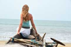 Girl sitting on the old fishing boat. Rajbag beach of South Goa, India Royalty Free Stock Photos