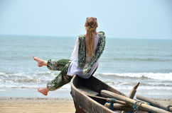Girl sitting on the old fishing boat. Rajbag beach of South Goa, India Royalty Free Stock Photo