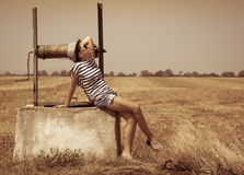The girl sitting on an old well Royalty Free Stock Photos