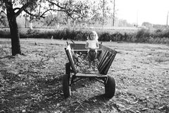 Girl sitting on an old wooden wagon in the village Stock Photography