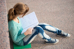Free Girl Sitting On Stairs And Reading Note Royalty Free Stock Photography - 55149797