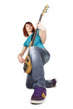 Girl sitting on one knee and playing bass guitar. Young beauty redhead girl sitting on one knee and playing bass guitar, full body, isolated stock image