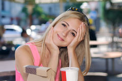 Girl sitting in an outdoor cafe and smiles Royalty Free Stock Photography