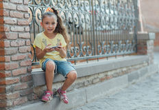 Girl is sitting outdoor and playing on the phone Stock Images