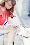 Girl sitting outdoors with a laptop and holding a smartphone in Stock Photo