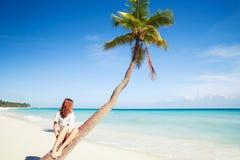 Girl sitting on a palm tree. Saona island beach. Atlantic ocean coast, Dominican Republic Royalty Free Stock Image