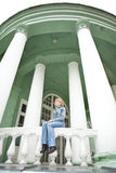 Girl sitting on parapet with white columns Stock Image